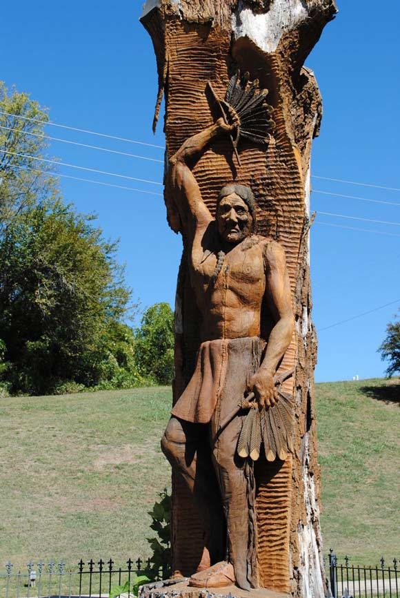 red indian carved in tree