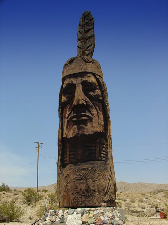 sad red indian face carving