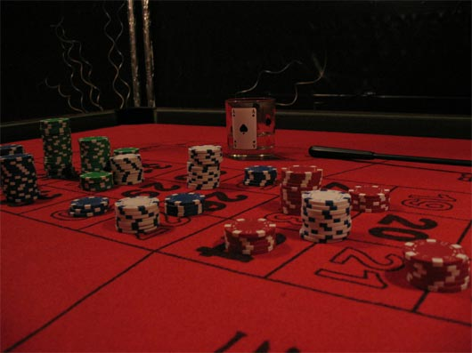 Casino roulette table with coins and glass Artistic Designs Collection of Casino Tokens